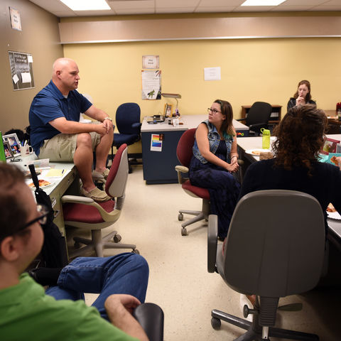 Graduate students talk in the student lounge.
