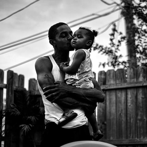 Exhibition images for Nurturing Positivity and Strength. Black and white photo of a Black father and his daughter by Donald Black Jr and a drawing of a Black father holding his child's hand by Dareece Walker.