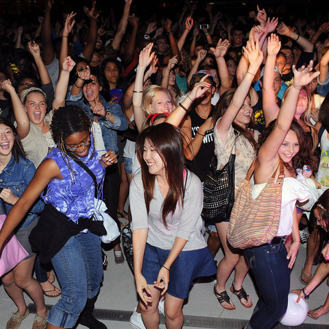 Students celebrate and throw their hands in the air at a campus event
