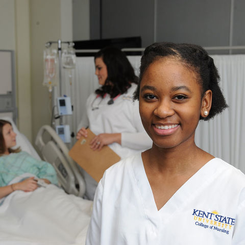 A Kent State nursing student poses as another nursing student cares for a patient in the background