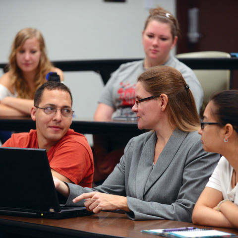 A faculty member works with students in the classroom.