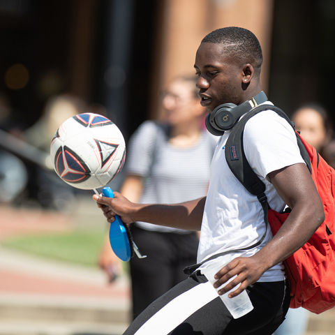A Student Plays with a Soccer Ball on Risman Plaza