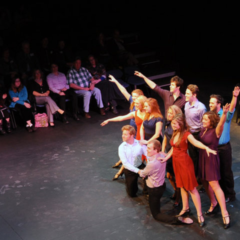 Students are gathered on a stage in poses as part of a play.  An audience sits to their right.