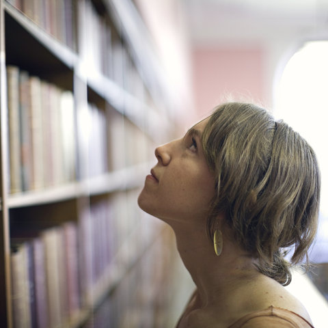 A student looks at a bookshelf of career guides and resources