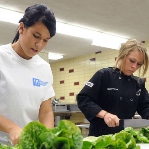 Two female students stand next to each other as they chop up lettuce in a kitchen.