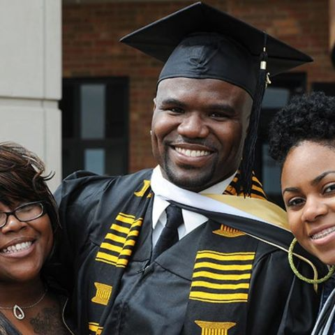 A male student in cap and gown smiles for a photo after having just graduated.  At his left and right shoulders are members of his family.