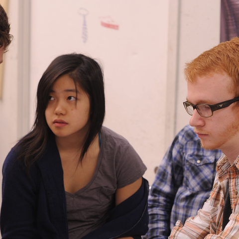 A group of students look intently at a computer screen