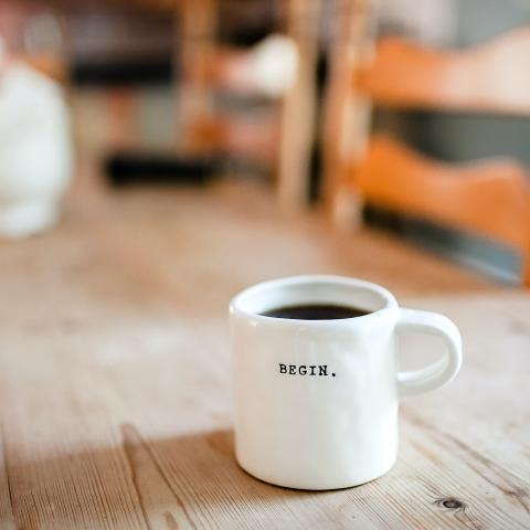 """Coffee mug on a table that reads """"begin."""""""