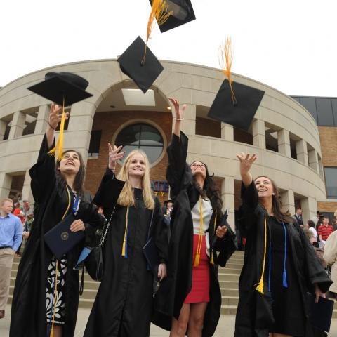 New Kent State graduates celebrate by throwing their caps in the air