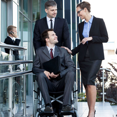 A man in a wheelchair greets a potential employer. He is wearing a suit and tie, and is holding a portfolio.