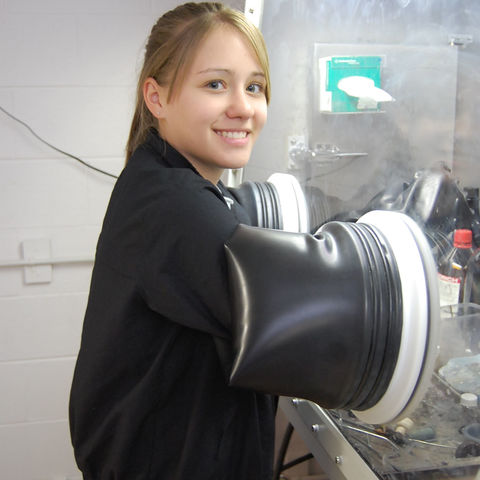 An undergraduate student performs research in a lab.