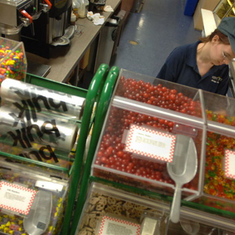 A female student employee stands behind a counter.  On the counter are plastic cases containing various types of candy.