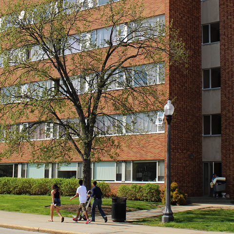Outdoor view of Korb Hall.  A group of students are walking in front of the building.
