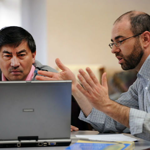 Two men are sitting at a table, facing a laptop computer screen.  One man is motioning with his hands as if to explain something.