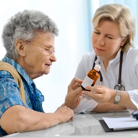 A Nurse Practitioner shows an elderly patient her medicine dosage