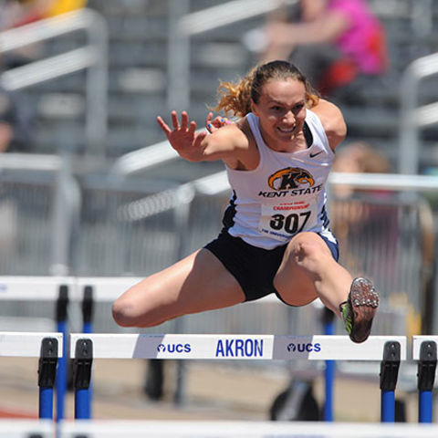 A female student athlete is jumping over a hurdle.