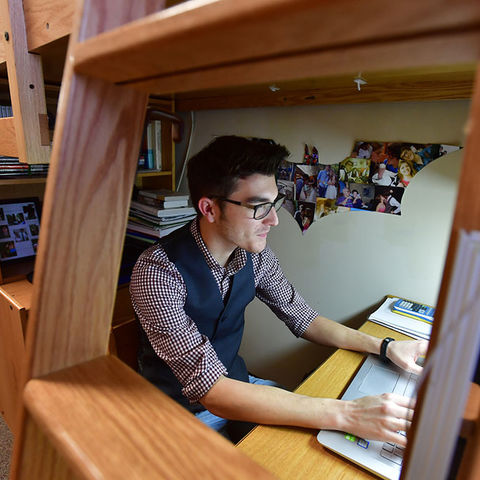 A student works on his laptop in his dorm