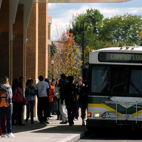 Students are lined up along a sidewalk, waiting in line to get on board a PARTA bus, which is parked in front of them.