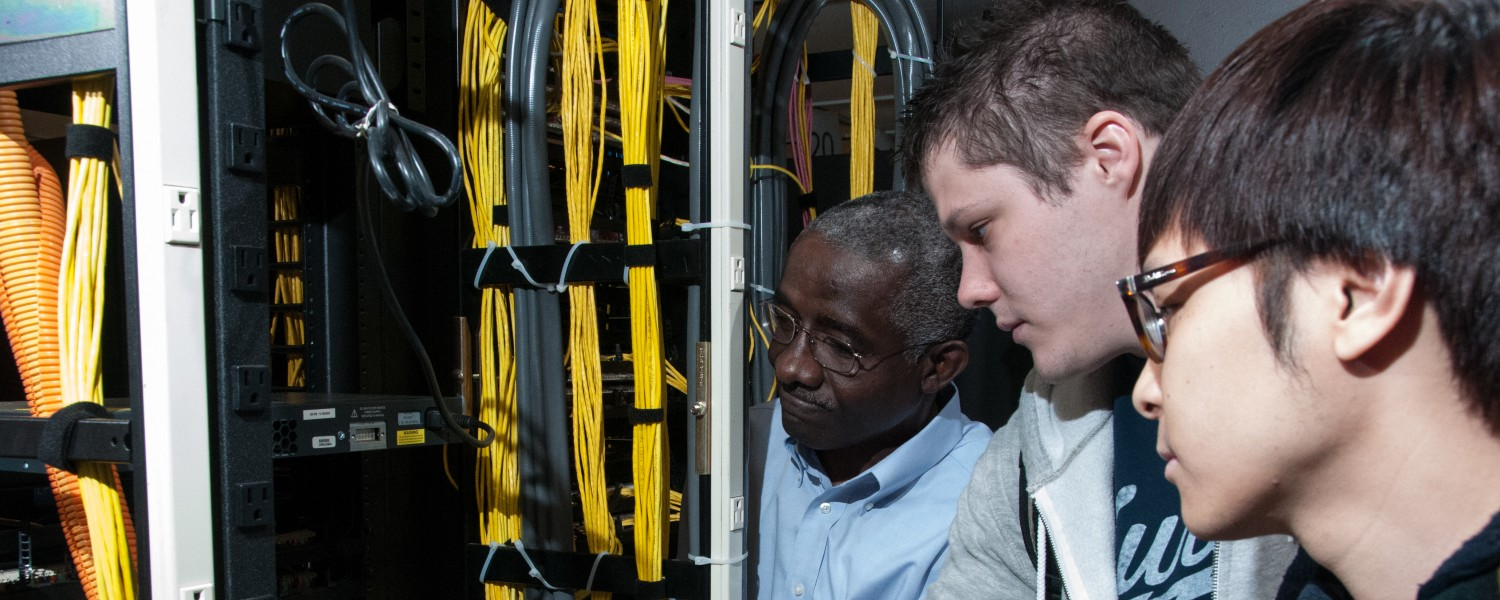 CAEST / DSCI Professor Gus Samba Examines Networking Equipment with a Group of DSCI Students