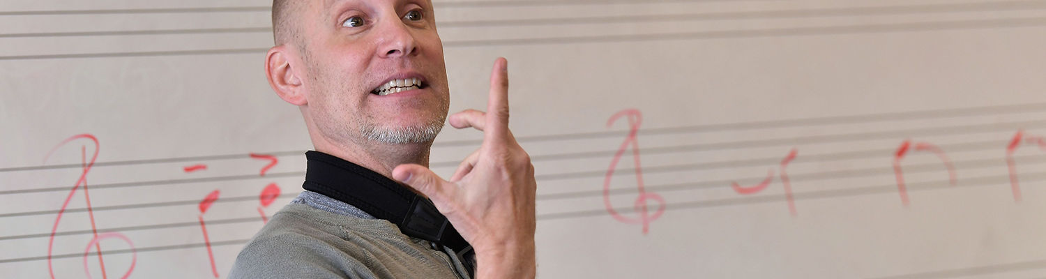 Music instructor in front of a white board with staff and musical notes written on it