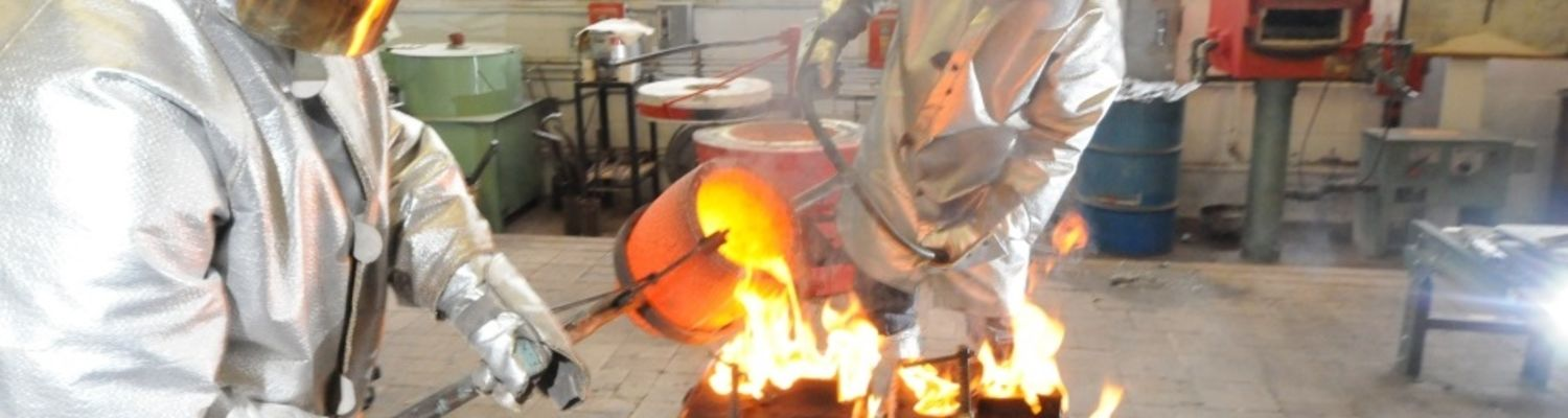 Students pouring molten metal in the Foundry