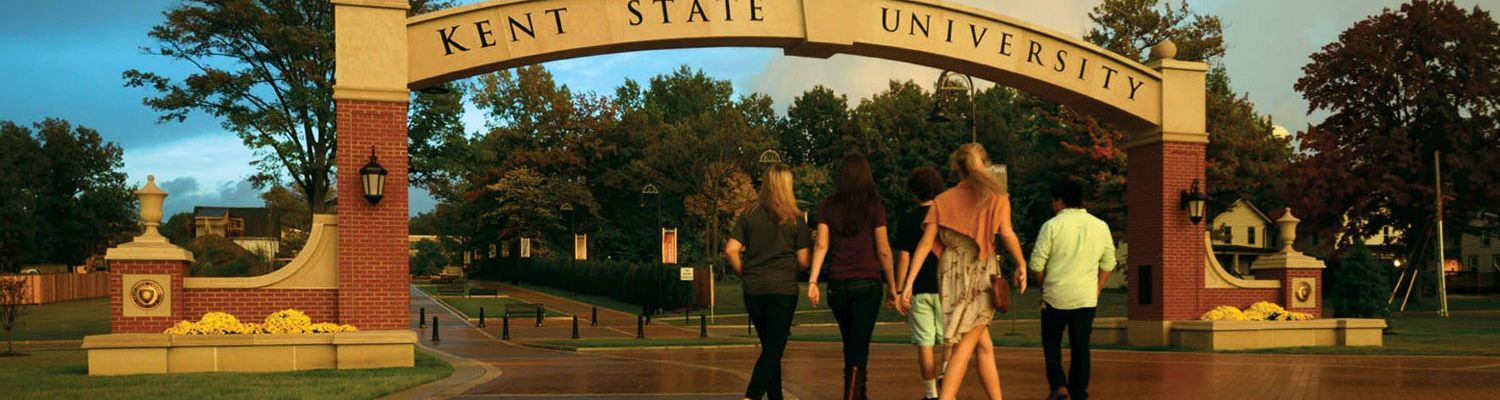 Students walking under the Kent State University arch