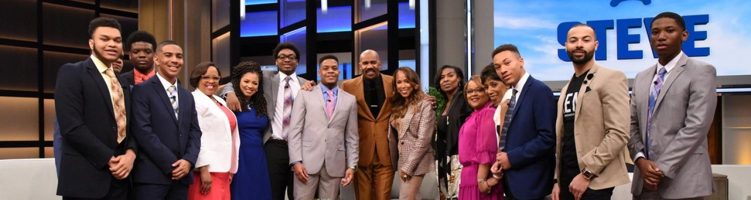 """Steve and Marjorie Harvey (middle) are surrounded by the eight scholarship recipients who will be attending Kent State in the fall and university staff members who accompanied them to the show. (Photo provided by the """"Steve"""" television show)"""