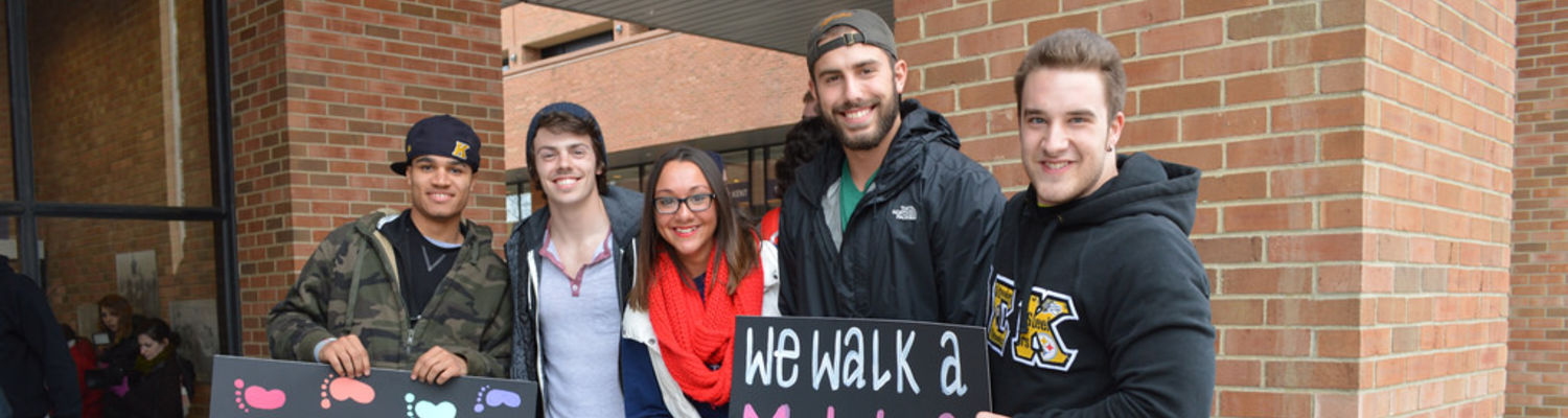 Students hold signs in front of the Student Center to promote the Walk a Mile event