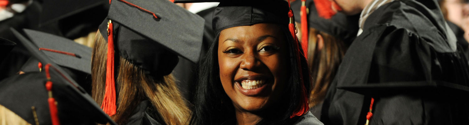 A student smiles and claps during commencement ceremonies being held at the MAC Center.