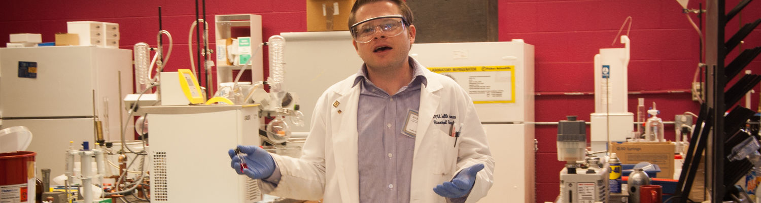 A graduate student shows Explore Kent Chemistry Day attendees around his lab and performs demonstrations.