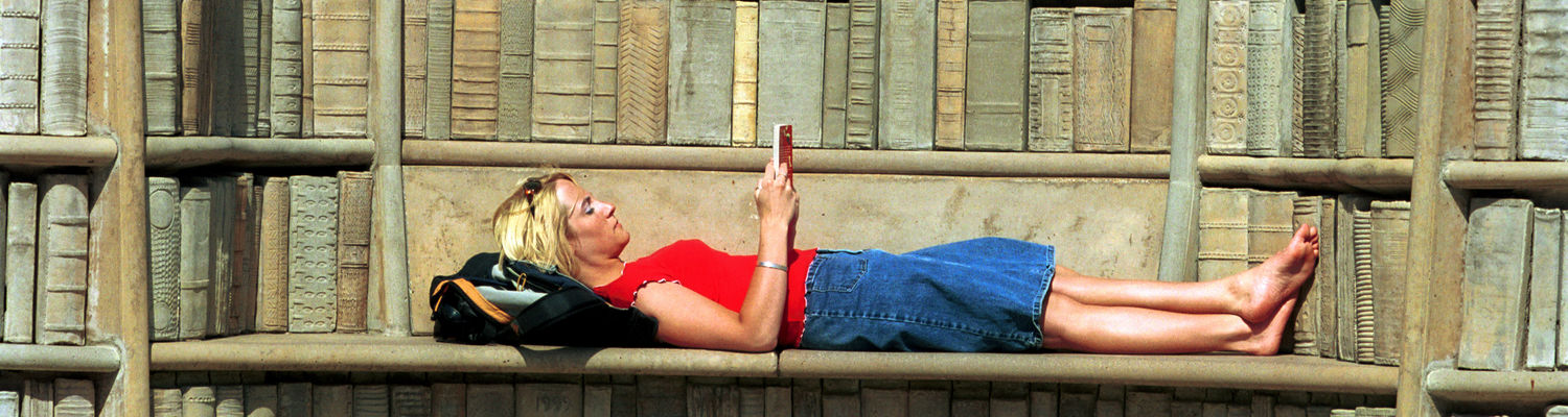 """An intervention specialist major in the College of Education and a Founder's Scholar reads and relaxes in the """"Behind the Brain Plaza"""" at Merrill Circle."""
