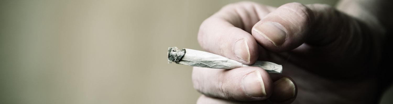 Hand holding a marijuana joint.