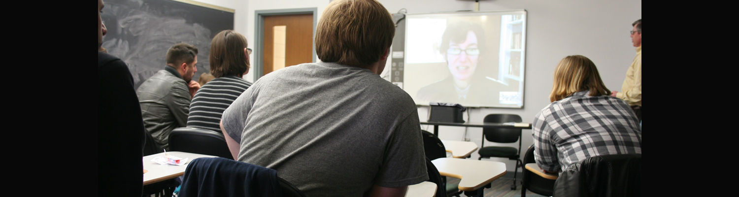 Image of Senior Seminar in IR/Comparative classroom with Dr. Barnes. On the students chat live with author Valeria Spering.