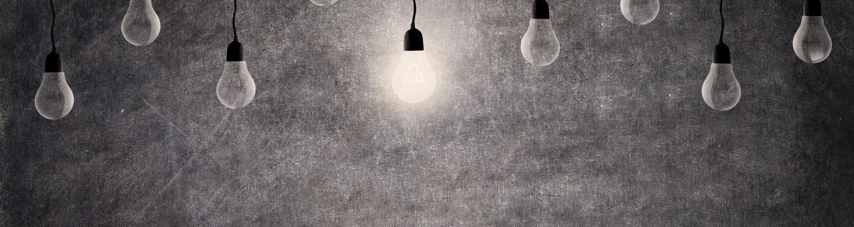 nine lightbulbs hanging from ceiling against chalkboard background one light bulb lit amongst others