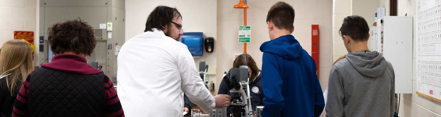 Science professor teaching students in lab