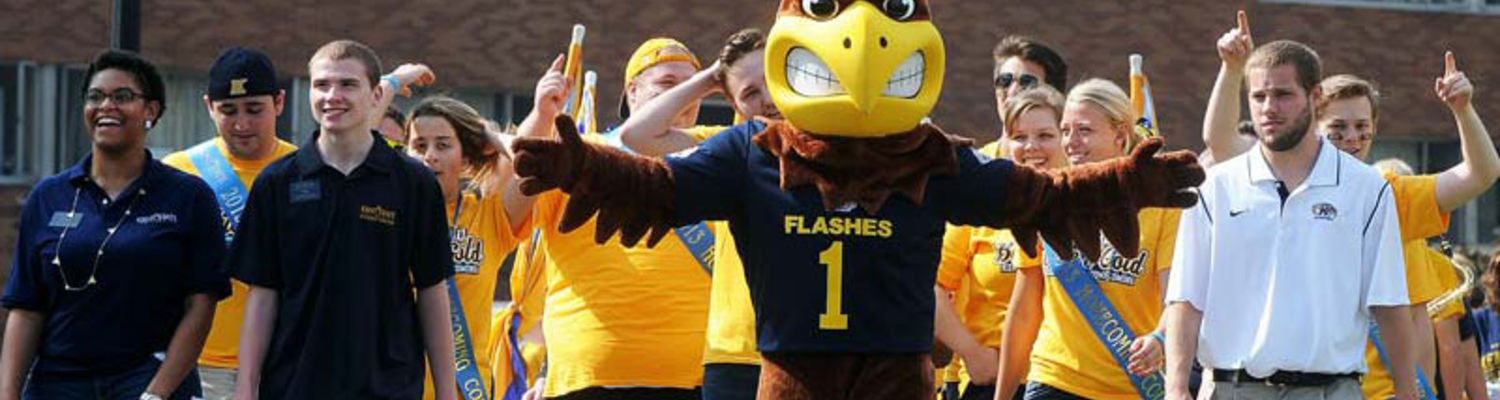 Kent State's mascot Flash welcomes new freshmen students with open arms.  A group of students stand behind him, looking excited.
