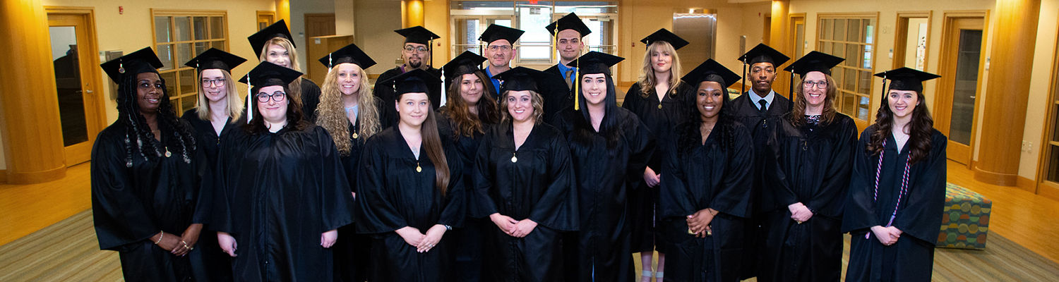 Group of students in graduation gowns standing in a room