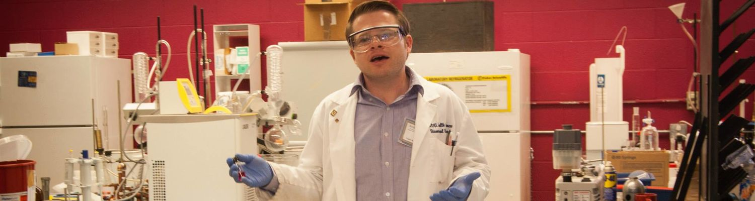 A graduate student gives Explore Kent Chemistry attendees a tour of his lab.