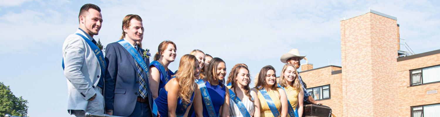 The students of homecoming court pose on a horse-drawn cart