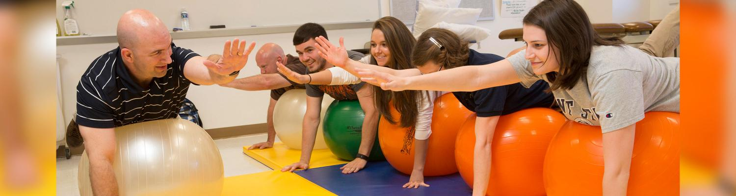 Photo of students in class, stretching on a balance ball