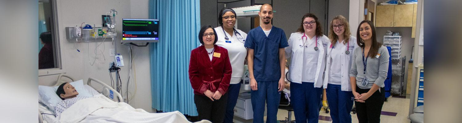 Photo of students standing in mock hospital room, posed for the camera