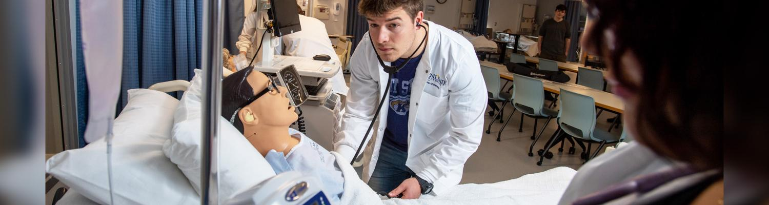 Photo of student in a classroom hospital setting with a pretend patient