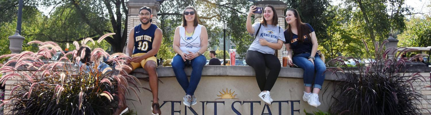 Students sit and smile on Kent State's front campus.