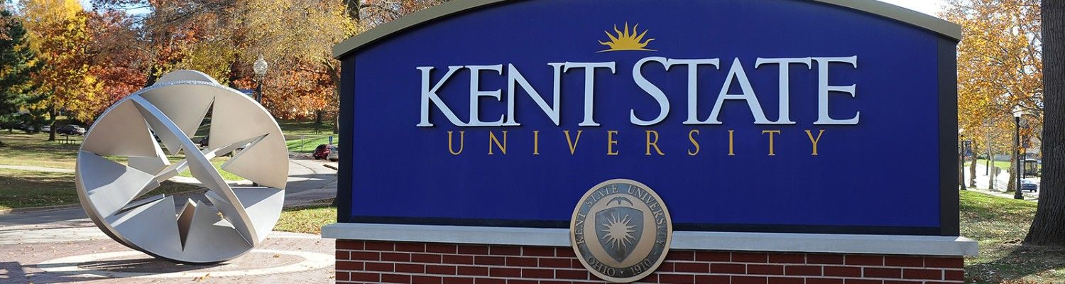 A Kent State University sign on front campus with a sculpture behind it