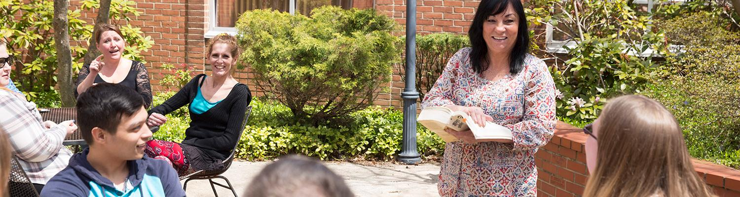 Photo of professor outside, engaging with students