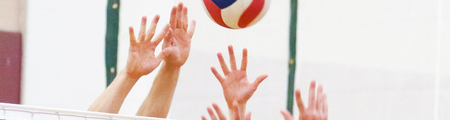 Several hands reach up to hit a volleyball as it flies over the net.