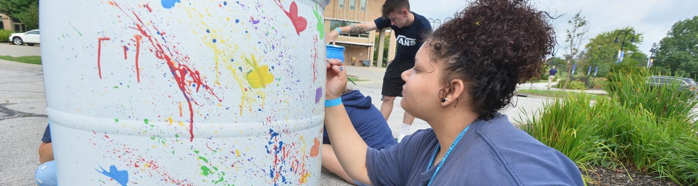 Students paint rain barrels on campus