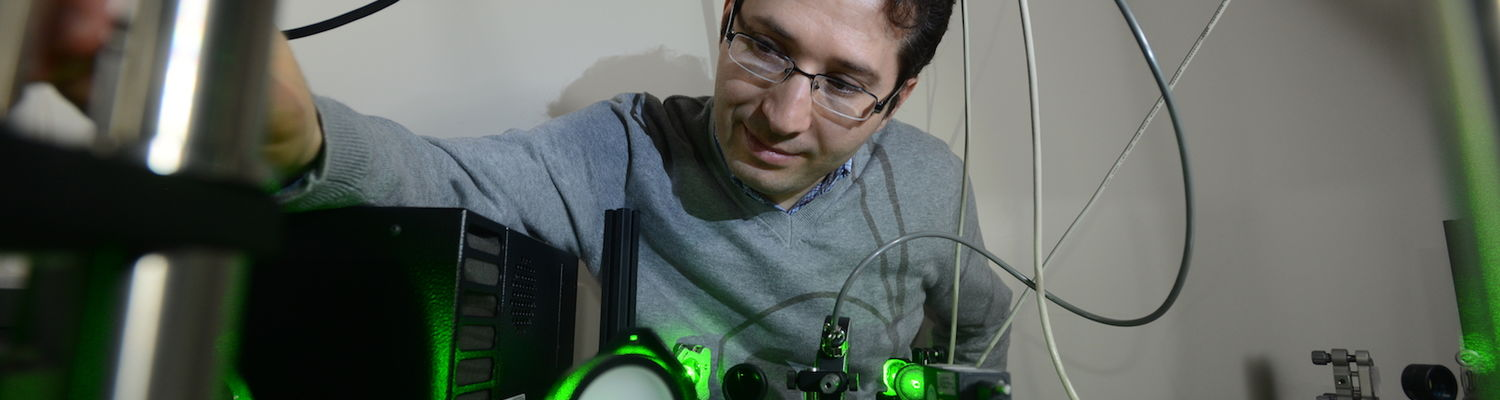 Dr. Hamza Balci, Associate Professor of Physics at Kent State, works with microscopy equipment in his lab.