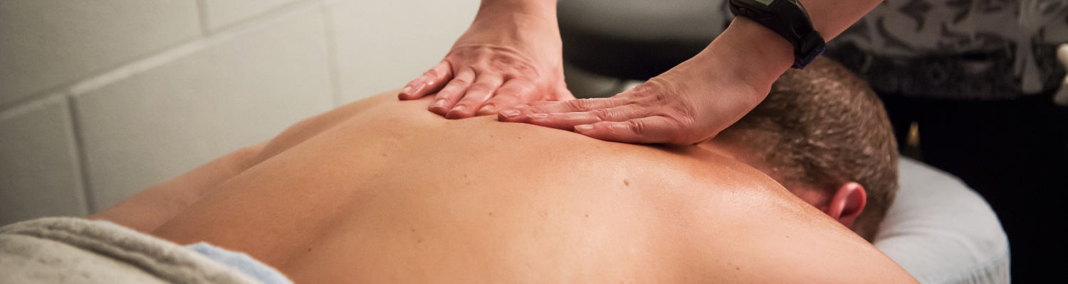A pair of hands press against the upper back of a man receiving a massage on a massage table