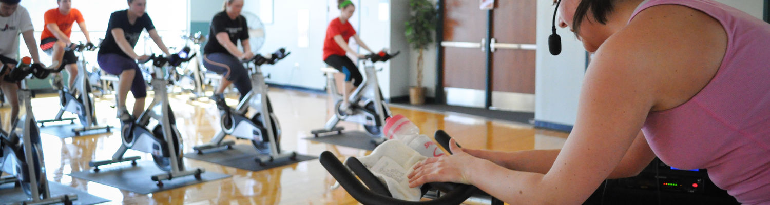 An instructor leads a class of students on stationary bikes in a fitness studio room